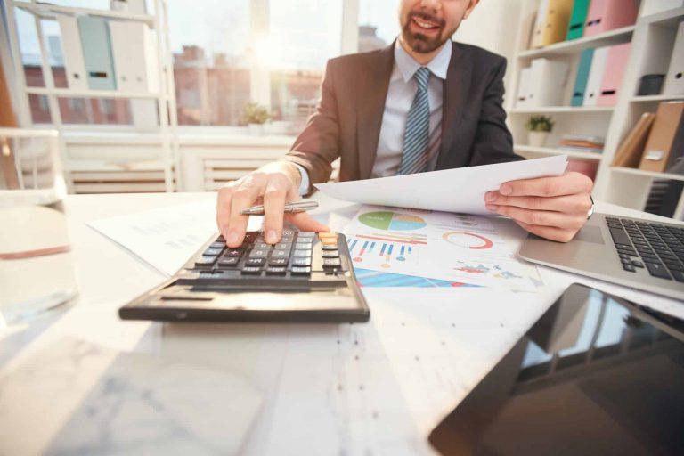 smiling-businessman-calculating-finances-closeup.jpg